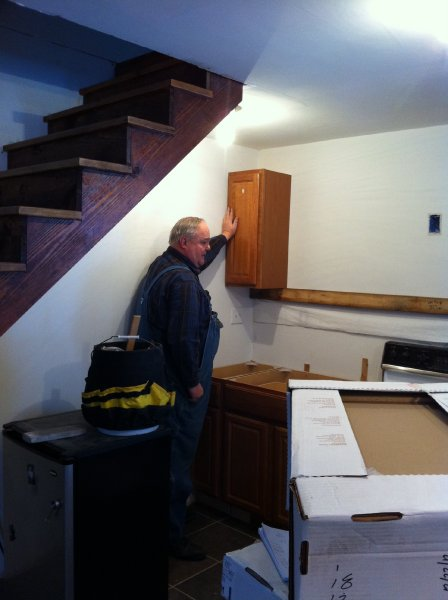 8 - My father hanging the first cabinet (Thanks, Pops!)
