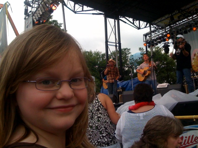 Alex smiles while Tracy Lawrence is on stage